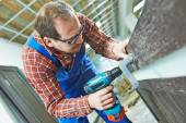 Carpenter works with drill — Stock Photo