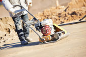 Worker with vibration compactor — Stock Photo