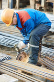 Worker cutting rebar by grinding machine — Stock Photo
