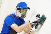 Plasterer worker with sander at wall filling — Stock Photo