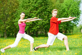 Fitness man and woman doing stretching exercises — Stock Photo