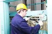 Machinist with spanner adjusting lift mechanism — Stock Photo