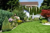 Landscape design of garden with grass and flowers — Stock Photo