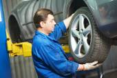 Auto mechanic screwing car wheel by wrench — Stock Photo