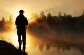 Fisher fishing on foggy sunrise — Stock Photo