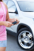 Woman with ignition key standing near new car — Foto Stock