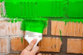Paint brush on brick wall — Stock Photo
