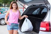 Woman shopper loading bag in trunk — ストック写真