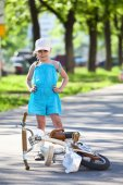Girl standing near a bicycle — Stock Photo