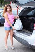 Woman with shopping bag loading suv — Zdjęcie stockowe