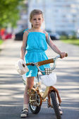 Girl standing with bicycle — Stock Photo