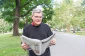Starszy mężczyzna czytanie gazety w parku — Zdjęcie stockowe
