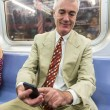 Senior Businessman Using Mobile Phone in the Subway Train — Stock Photo #53559147