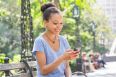 Beautiful Mixed Race Young Woman Typing on Mobile Phone — Stock Photo
