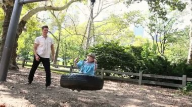 Father pushing daughter on swing — Stock Video