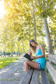 Beautiful Young Woman Reading a Book at Park — 图库照片
