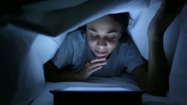 Furtive Woman Using Digital Tablet under Bed Sheets — Stock Video