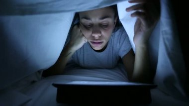 Tired Woman Using Digital Tablet under Bed Sheets — Stock Video