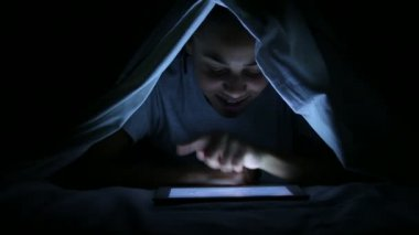 Beautiful Woman Using Digital Tablet under Bed Sheets — Stock Video