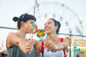 Happy Young Women eating Lollipop — Stock Photo