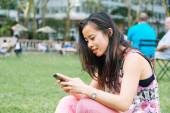 Girl Typing on Phone at Park — Stock Photo