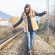 Beautiful Young Woman Walking in Balance on Railway Tracks. The — Stock Photo #64556487