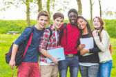 Group of multiethnic teenage students embraced together at park. — Stock Photo