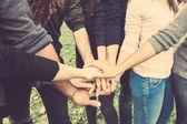 Multiracial grupo de amigos com as mãos na pilha — Fotografia Stock
