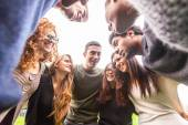 Multiracial group of friends embraced in a circle — Stock Photo
