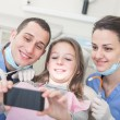 Happy patient, dentist and assistant taking selfie all together — Stock Photo #65769875