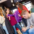 Bored man in a clothes shop waiting for women — Stock Photo #65774747