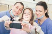 Happy patient, dentist and assistant taking selfie all together — Stock Photo