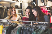 Three women in a clothing store choosing a dress — Stock Photo