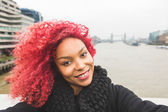 Girl taking selfie in London with Tower Bridge on background — Stockfoto