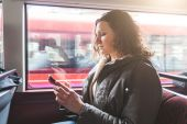 Beautiful woman typing on smart phone while commuting in London — Stock Photo