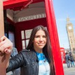 Young woman  in London with phone booth and Big Ben — Stock Photo #70996633