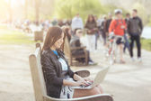 Young woman using computer at park in London — Stock Photo