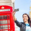 Young woman  in London with phone booth and Big Ben — Stock Photo #71042077