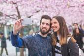 Hipster couple taking a selfie in Stockholm with cherry blossoms — Stock Photo