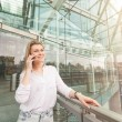 Young woman talking on mobile phone with a glazed background — Stock Photo #71943903