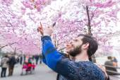 Hipster couple taking photos of cherry blossoms in Stockholm — Stock Photo