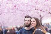 Hipster couple portrait in Stockholm with cherry blossoms — Stock Photo