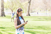 Young woman listening music at park in London — Stock Photo