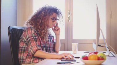 Joven mujer que trabaja en casa o en una pequeña oficina — Vídeo de Stock