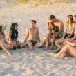 Group of friends singing on the beach at sunset. — Stock Photo #76556879