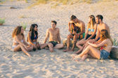 Group of friends singing on the beach at sunset. — Stock Photo