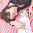 Young mother lying down and embracing her little daughter. — Stock Photo #76807129