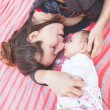 Young mother lying down and embracing her little daughter. — Stock Photo #76808503