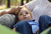 Boy resting on mother leg — Foto de Stock