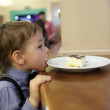 Child licking plate with cake — Foto de Stock   #61685055